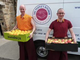 Two monks from Pathgate Institute delivering fruit to the People's Kitchen